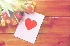 Fermez-vous des fleurs et de la carte de voeux avec le coeur Images libres de droits