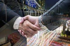 Fermez-vous des gens d'affaires de poignée de main sur la grande ville Photographie stock libre de droits