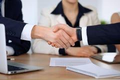 Fermez-vous des gens d'affaires se serrant la main à la réunion ou à la négociation dans le bureau Les associés sont satisfaisant Photo stock