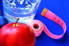 Fermez-vous des haltères rouges transparentes d'une pomme deux et de l'eau en verre Image stock