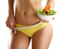 Fermez-vous des hanches de mesure d'une femme avec de la salade dans sa main Images stock