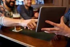 Fermez-vous des hommes avec le PC et la bière de comprimé à la barre Image libre de droits