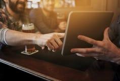 Fermez-vous des hommes avec le PC et la bière de comprimé à la barre Photographie stock libre de droits