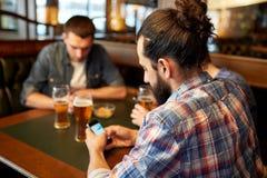 Fermez-vous des hommes avec les smartphones et la bière à la barre Images stock