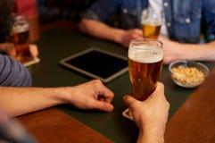 Fermez-vous des hommes buvant de la bière à la barre ou au bar Photos stock