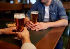 Fermez-vous des hommes buvant de la bière à la barre ou au bar Photographie stock