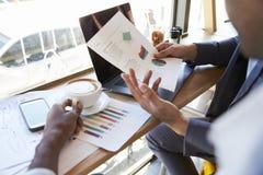 Fermez-vous des hommes d'affaires discutant le document dans le café Images stock