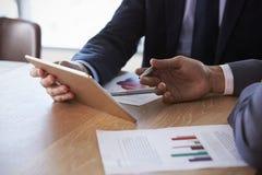 Fermez-vous des hommes d'affaires utilisant la Tablette de Digital lors de la réunion Images libres de droits
