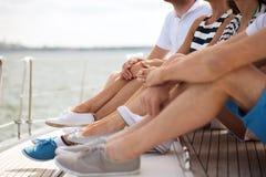 Fermez-vous des jambes d'amis se reposant sur la plate-forme de yacht Image stock