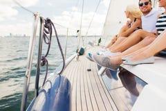 Fermez-vous des jambes d'amis se reposant sur la plate-forme de yacht Photo stock