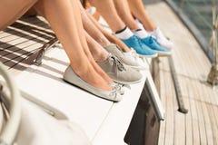 Fermez-vous des jambes d'amis se reposant sur la plate-forme de yacht Photographie stock libre de droits