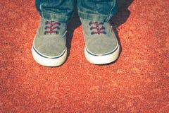 Fermez-vous des jambes d'enfant avec des espadrilles et des jeans Fond rouge de terrain de jeu Photographie stock