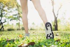 Fermez-vous des jambes d'une jeune femme en réchauffant le corps en étirant ses jambes avant exercice et yoga de matin sur l'herb Photo libre de droits