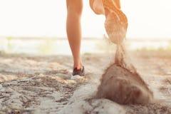 Fermez-vous des jambes d'une jeune femme qui coule de la route en parc Image libre de droits