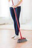 Fermez-vous des jambes de femme avec le plancher rapide de balai Photographie stock