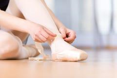 Fermez-vous des jambes de la ballerine laçant les pointes images stock