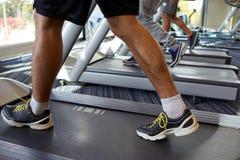 Fermez-vous des jambes des hommes marchant sur des tapis roulants dans le gymnase Image stock