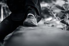 Fermez-vous des jambes humaines portant les chaussures noires Photo stock