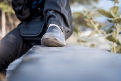 Fermez-vous des jambes humaines portant les chaussures noires Image stock