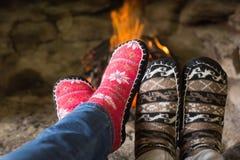 Fermez-vous des jambes romantiques dans les chaussettes devant la cheminée Photographie stock libre de droits