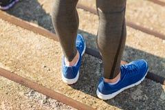Fermez-vous des jambes sportives d'homme dans des chaussures sur des escaliers Images libres de droits