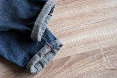 Fermez-vous des jeans de denim de lisière de pli sur le fond en bois avec images libres de droits