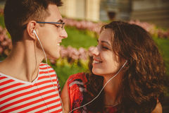 Fermez-vous des jeunes couples heureux ayant l'amusement au parc tout en écoutant la musique Photographie stock