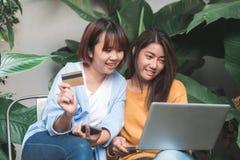Fermez-vous des jeunes femmes asiatiques d'un couple employant sa carte de crédit tandis qu'ils font l'achat en ligne avec son or photos stock
