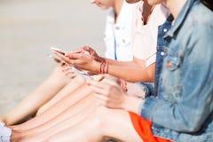 Fermez-vous des jeunes femmes avec des smartphones sur la plage Image libre de droits