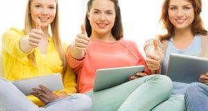 Fermez-vous des jeunes femmes avec le PC de comprimé à la maison Image stock