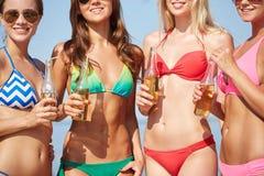 Fermez-vous des jeunes femmes buvant de la limonade sur la plage Photo stock