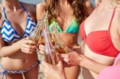 Fermez-vous des jeunes femmes heureuses avec des boissons sur la plage Image stock