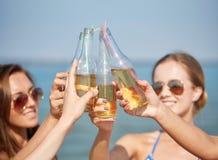 Fermez-vous des jeunes femmes heureuses avec des boissons sur la plage Photos libres de droits