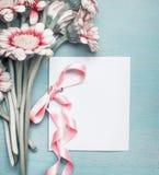 Fermez-vous des jolies fleurs sur le fond chic minable de bleu de turquoise et raillez de la carte de voeux avec le ruban rose Photos stock