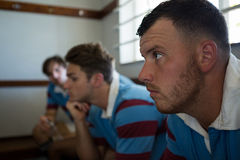 Fermez-vous des joueurs réfléchis de rugby semblant partis tout en se reposant contre le mur Photographie stock
