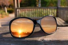 Fermez-vous des lunettes de soleil noires brillantes sur la balustrade du belvédère avec le coucher du soleil se reflétant dans d photographie stock libre de droits