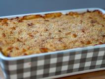 Fermez-vous des macaronis au fromage cuits au four dans un plat de cocotte en terre images libres de droits