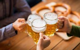 Fermez-vous des mains avec des tasses de bière à la barre ou au bar Photos stock
