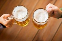 Fermez-vous des mains avec des tasses de bière à la barre ou au bar Photographie stock libre de droits