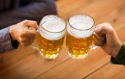 Fermez-vous des mains avec des tasses de bière à la barre ou au bar Images libres de droits