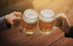 Fermez-vous des mains avec des tasses de bière à la barre ou au bar Images stock
