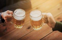Fermez-vous des mains avec des tasses de bière à la barre ou au bar Image stock