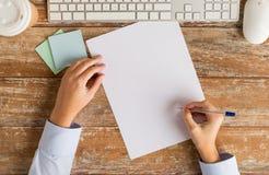 Fermez-vous des mains avec la feuille et le clavier de papier Photo stock