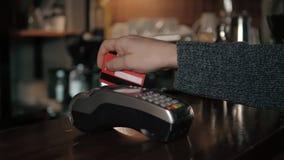 Fermez-vous des mains avec le lecteur de carte de crédit au café moderne Photo libre de droits