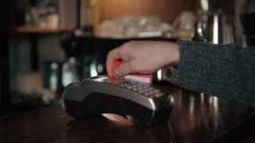 Fermez-vous des mains avec le lecteur de carte de crédit au café moderne Image libre de droits