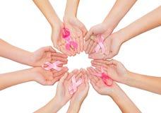 Fermez-vous des mains avec le symbole de conscience de cancer photographie stock libre de droits