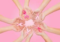 Fermez-vous des mains avec le symbole de conscience de cancer Photos libres de droits