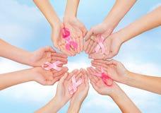 Fermez-vous des mains avec le symbole de conscience de cancer Photo stock