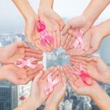 Fermez-vous des mains avec le symbole de conscience de cancer Photographie stock