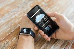 Fermez-vous des mains avec le téléphone et la montre intelligents Photographie stock